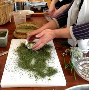 Rolling fresh goat cheese in dried nettles